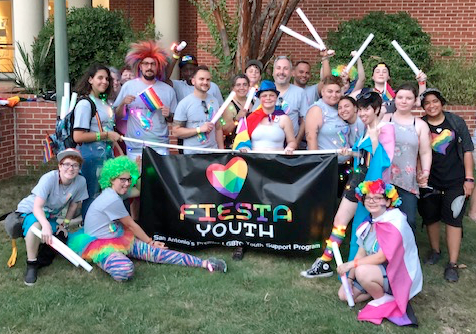 Youth and staff holding up a banner, dressed in pride outfits