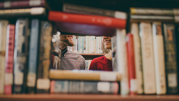 Two people meeting and smiling behind a bookshelf