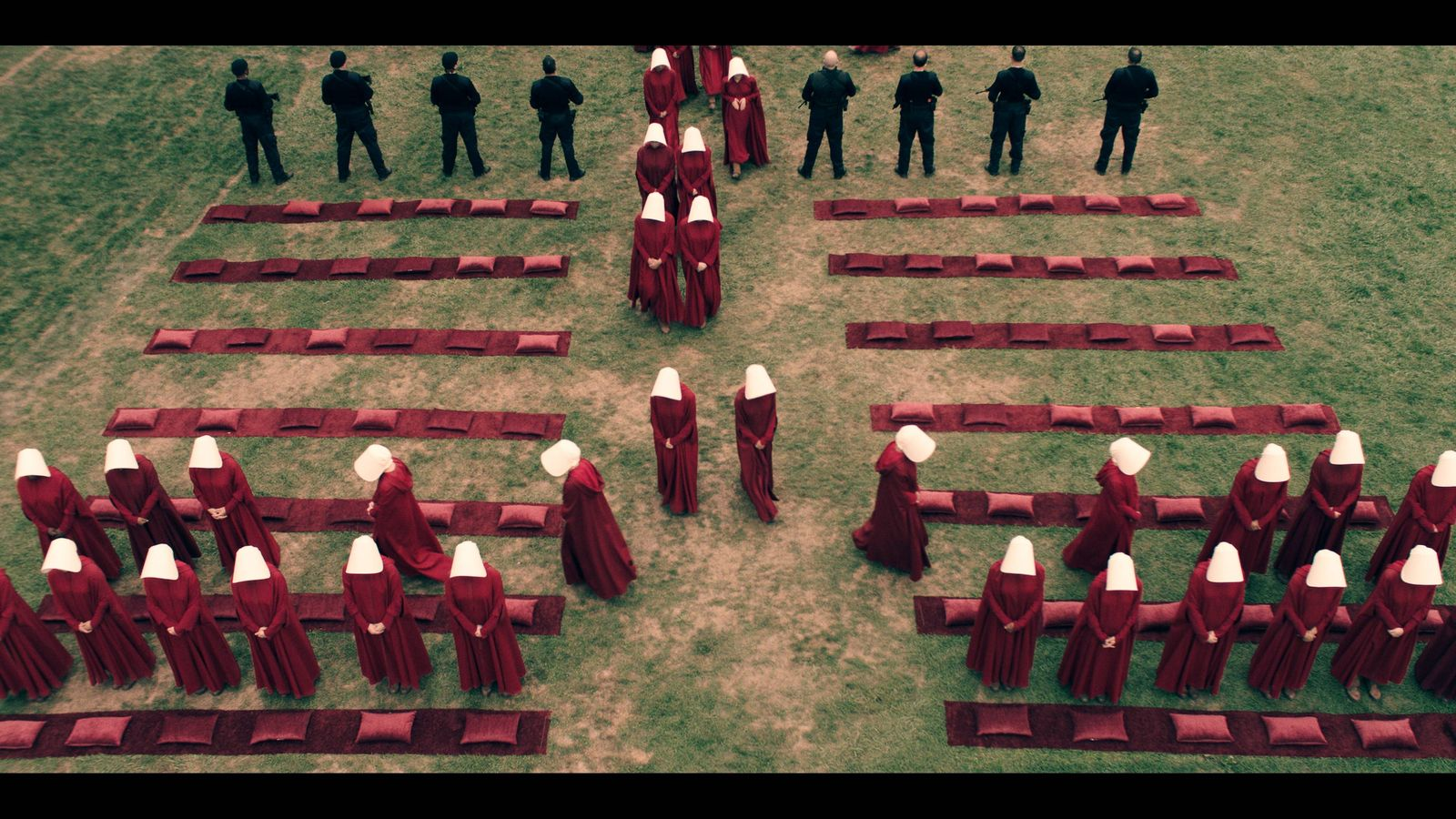 Image of handmaids filing into a grassy area, from the series.