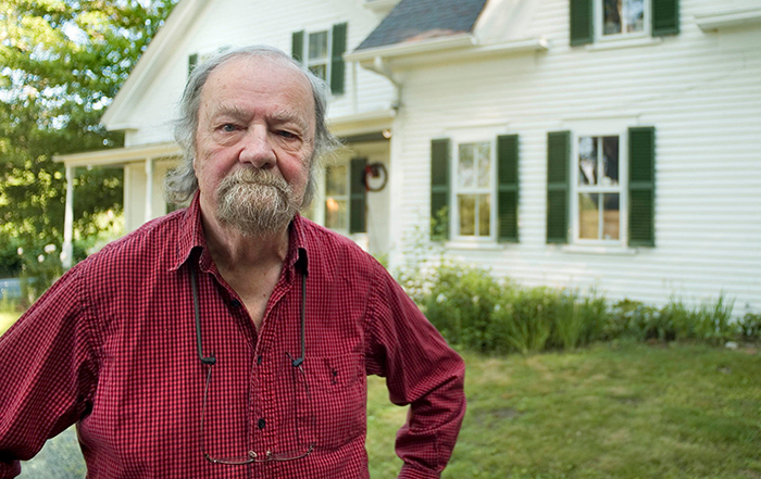 Donald Hall standing in front of a house